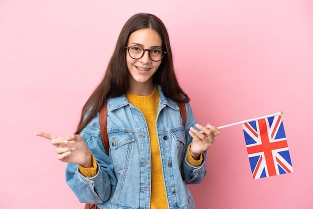 Junges französisches mädchen, das eine flagge großbritanniens lokalisiert auf rosa hintergrund zeigt finger zur seite zeigt