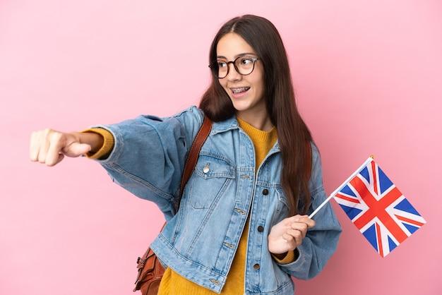 Junges französisches mädchen, das eine großbritannienflagge lokalisiert auf rosa hintergrund hält, der eine daumen hoch geste gibt