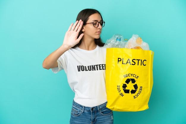 Junges französisches mädchen, das eine tasche voll von plastikflaschen hält, um zu recyceln, stoppgeste zu machen und enttäuscht