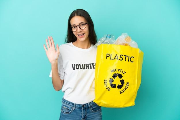 Junges französisches mädchen, das eine tasche voller plastikflaschen hält, um den gruß mit der hand mit glücklichem ausdruck zu recyceln