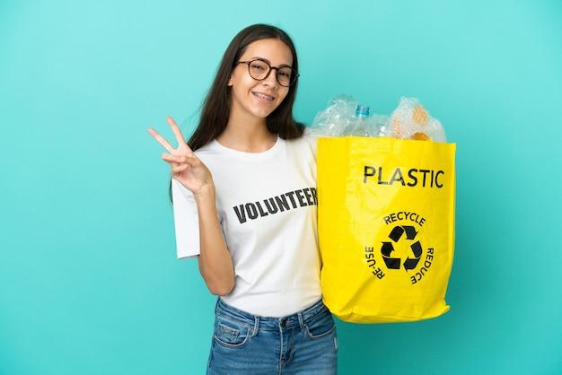 Junges französisches mädchen, das eine tasche voller plastikflaschen hält, um lächelnd zu recyceln und victory-zeichen zu zeigen