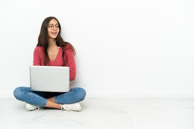 Junges französisches mädchen, das mit ihrem laptop mit verschränkten armen und glücklich auf dem boden sitzt