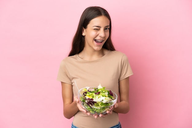 Junges französisches mädchen lokalisiert auf rosa hintergrund, der eine schüssel salat beim zwinkern hält