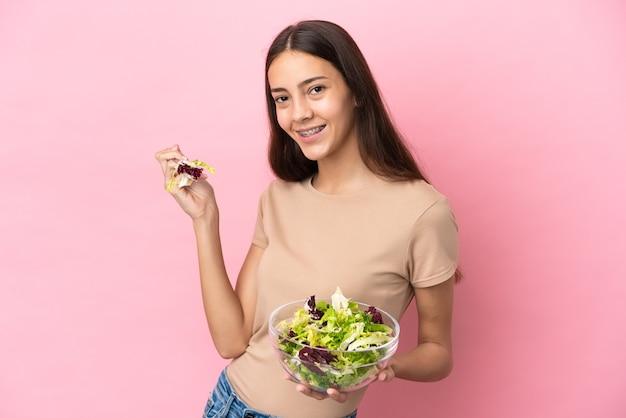 Junges französisches mädchen lokalisiert auf rosa hintergrund, der eine schüssel salat mit glücklichem ausdruck hält