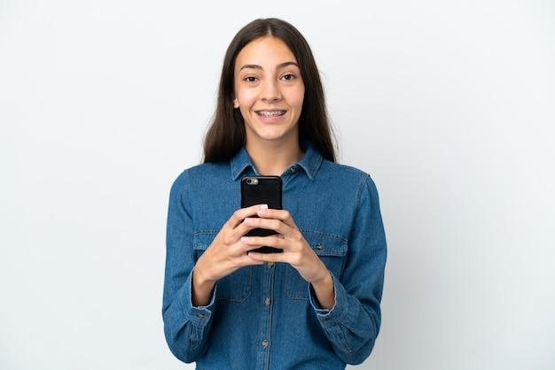 Junges französisches mädchen lokalisiert auf weißem hintergrund, der die kamera betrachtet und beim verwenden des handys lächelt