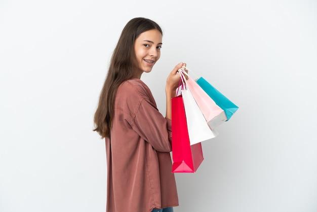 Junges französisches mädchen lokalisiert auf weißem hintergrund, der einkaufstaschen hält und lächelt