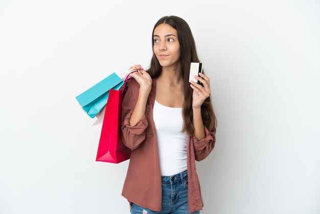 Junges französisches mädchen lokalisiert auf weißem hintergrund, der einkaufstaschen und eine kreditkarte hält und denkt