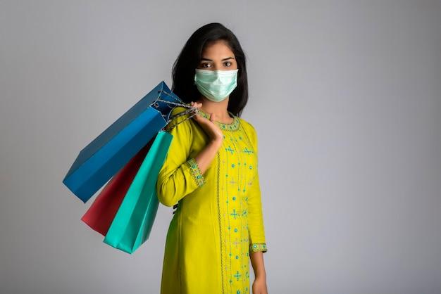 Junges frauenmädchen, das medizinische maske trägt, die einkaufstaschen auf grauem hintergrund hält. shopping discount sale konzept.