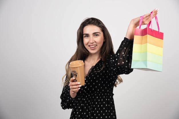 Junges frauenmodell, das eine geschäftstasche zeigt und eine kaffeetasse hält