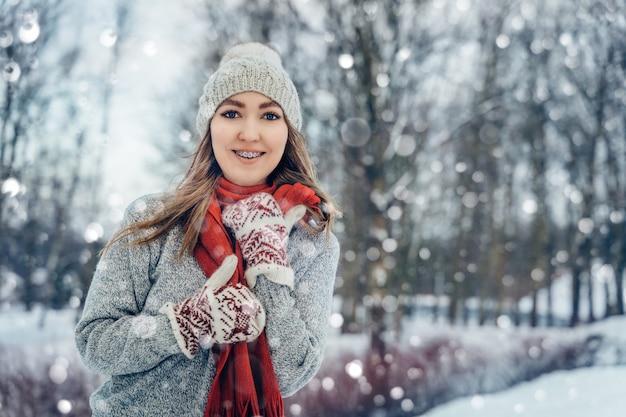 Junges frauenporträt des winters fröhliches modellmädchen, das im winterpark lacht und spaß hat