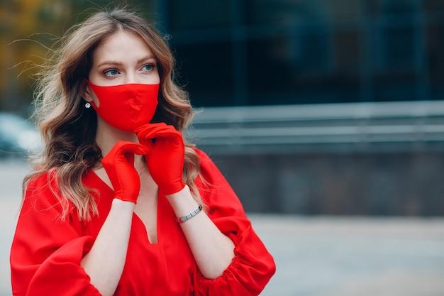 Junges frauenporträt im roten kleid und in den handschuhen setzt medizinische gesichtsmaske an der straße außerhalb auf
