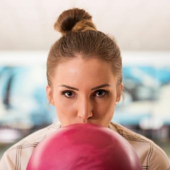 Junges frauenporträt mit rosa bowlingkugel