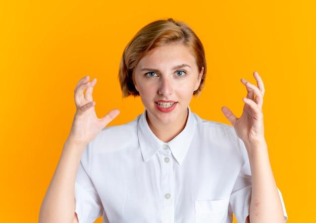 Junges freudiges blondes russisches mädchen steht mit erhobenen händen