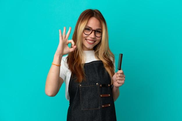 Junges friseurmädchen über isoliertem blauem hintergrund, das ein ok-zeichen mit den fingern zeigt