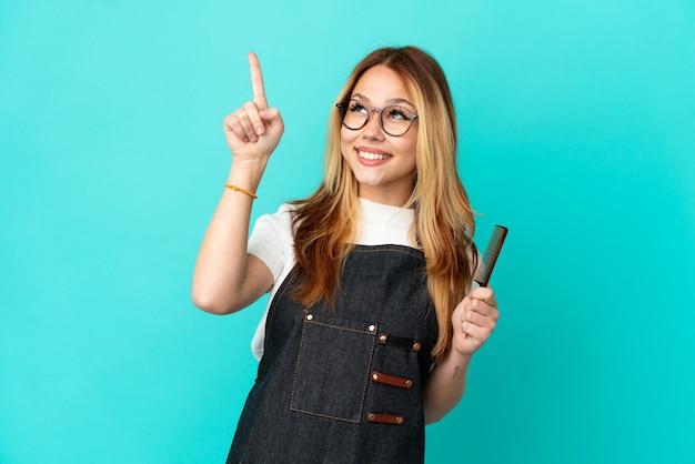 Junges friseurmädchen über isoliertem blauem hintergrund, das mit dem zeigefinger zeigt, eine großartige idee