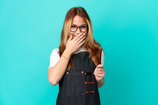 Junges friseurmädchen über isoliertem blauem hintergrund glücklich und lächelnd, den mund mit den händen bedeckend
