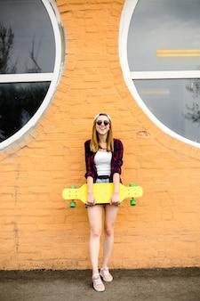 Junges fröhliches mädchen, das mit gelbem skateboard gegen orange wand aufwirft.