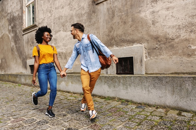Junges fröhliches multikulturelles hipster-paar, das in einem alten teil der stadt geht und hände hält.