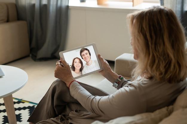 Junges fröhliches paar auf touchpad-anzeige, das mutter von einem von ihnen mit zahnigem lächeln während der online-kommunikation betrachtet
