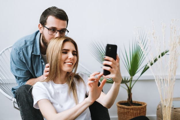 Junges fröhliches paar, das handy benutzt und selfie auf smartphone zusammen macht.