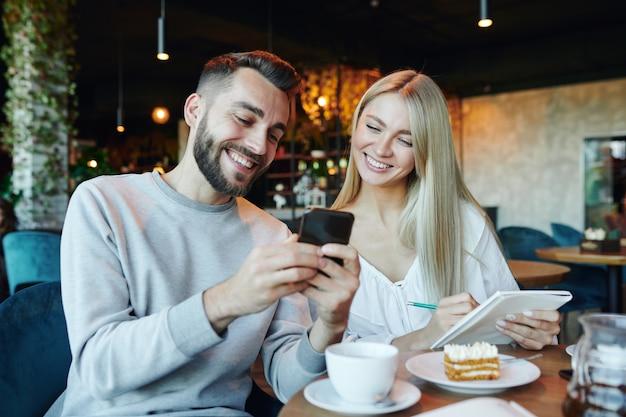 Junges fröhliches paar, das smartphonebildschirm beim sitzen am tisch im café betrachtet, plaudert und tee mit nachtisch hat