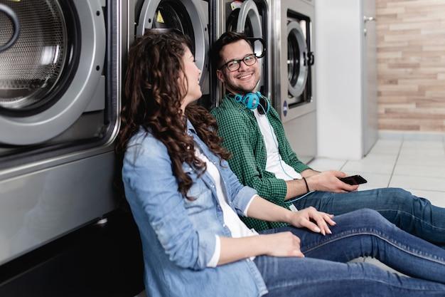 Junges fröhliches paar, das zusammen wäsche im waschsalon macht.