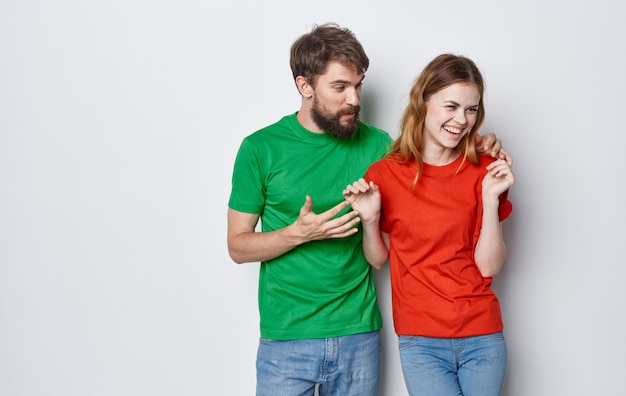 Junges fröhliches paar in mehrfarbigen t-shirts kommunikationsgefühle freundschaft