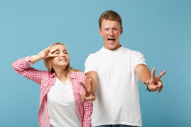 Junges fröhliches paar zwei freunde kerl mädchen in weißen rosa leeren leeren design t-shirts posiert
