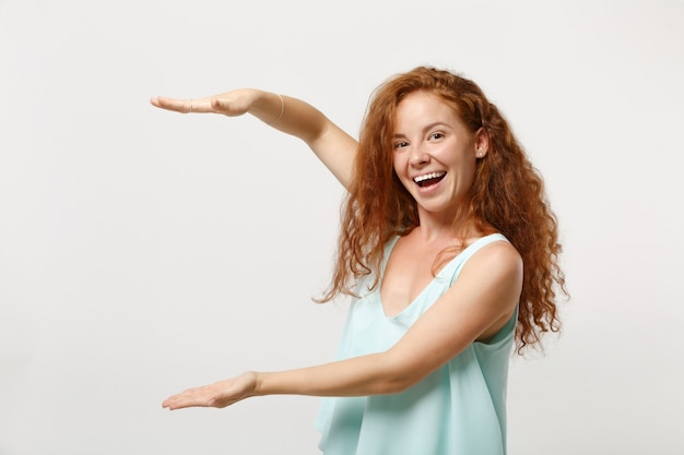 Junges fröhliches rothaarigefrauenmädchen in der zufälligen hellen kleidung, die lokalisiert auf weißem wandhintergrund aufwirft. menschen lifestyle-konzept. kopieren sie platz. gestikulieren, um größe mit vertikalem arbeitsbereich zu demonstrieren.