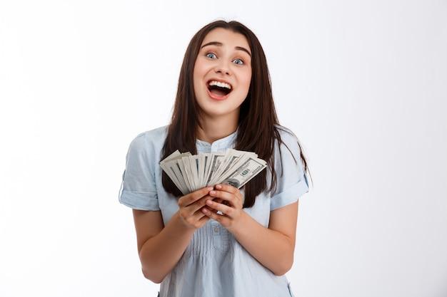 Junges fröhliches schönes geschäftsmädchen, das geld über weißer wand hält
