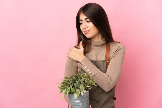 Junges gärtnermädchen, das eine pflanze lokalisiert auf rosa hintergrund hält, der unter schmerzen in der schulter leidet, weil sie sich bemüht haben