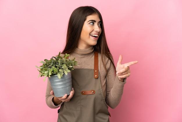 Junges gärtnermädchen, das eine pflanze lokalisiert auf rosa wand hält, die beabsichtigt, die lösung zu realisieren, während ein finger anhebt