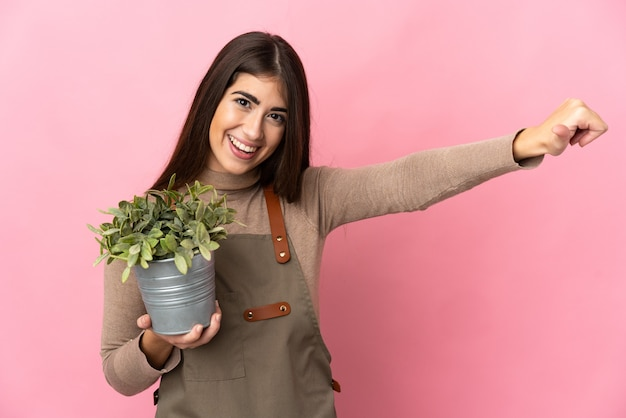 Junges gärtnermädchen, das eine pflanze lokalisiert auf rosa wand hält, die eine daumen hoch geste gibt