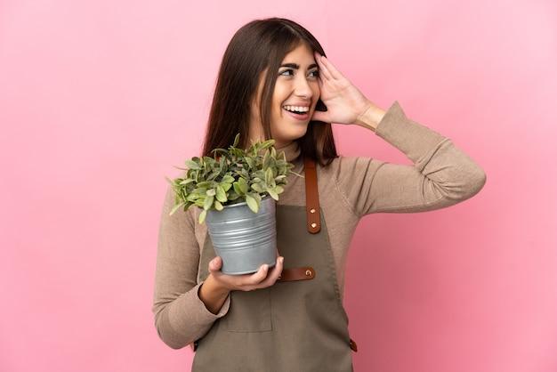 Junges gärtnermädchen, das eine pflanze lokalisiert auf rosa wand hält, die viel lächelt
