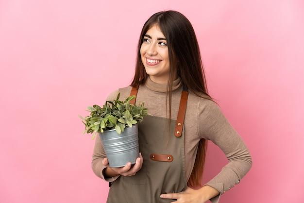 Junges gärtnermädchen, das eine pflanze lokalisiert auf rosa wand hält, die zur seite schaut und lächelt