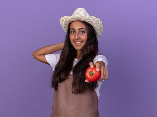 Junges gärtnermädchen in der schürze und im sommerhut, die frische tomaten mit lächeln auf gesicht halten, das über lila wand steht