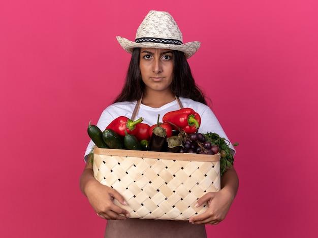 Junges gärtnermädchen in der schürze und im sommerhut, die kiste voller gemüse mit ernstem gesicht halten, das über rosa wand steht