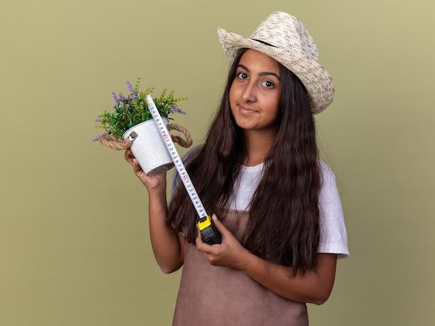 Junges gärtnermädchen in der schürze und im sommerhut, die maßband und topfpflanze halten, die es mit lächeln auf gesicht messen, das über grüner wand steht