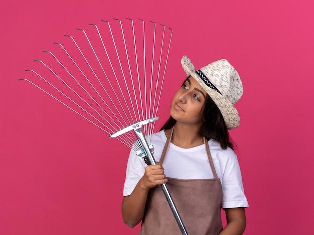 Junges gärtnermädchen in der schürze und im sommerhut, die rechen halten, der es mit lächeln auf gesicht betrachtet, das über rosa wand steht