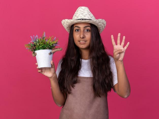 Junges gärtnermädchen in der schürze und im sommerhut, die topfpflanze lächelnd zeigt und nummer vier über rosa wand stehend zeigt