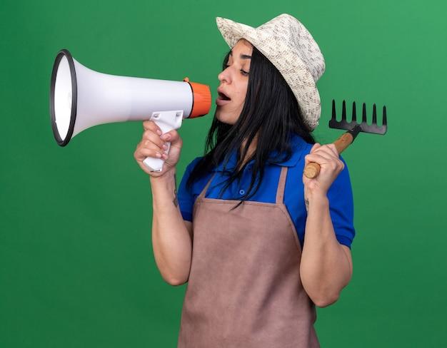 Junges gärtnermädchen in uniform und hut, das in der profilansicht steht und einen rechen hält, der vom lautsprecher spricht, der isoliert auf die grüne wand schaut