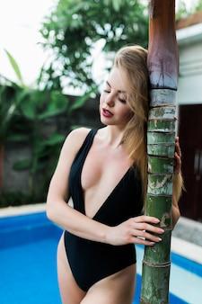Junges gebräuntes mädchen im schwarzen badeanzug, der im pool an tropischer villa entspannt