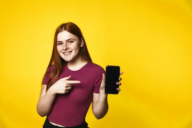 Junges gelächeltes kaukasisches mädchen der rothaarigen hält einen smartphone