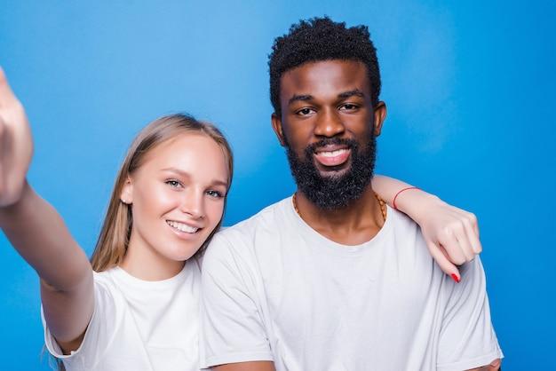 Junges gemischtes paar macht selfie isoliert auf blauer wand