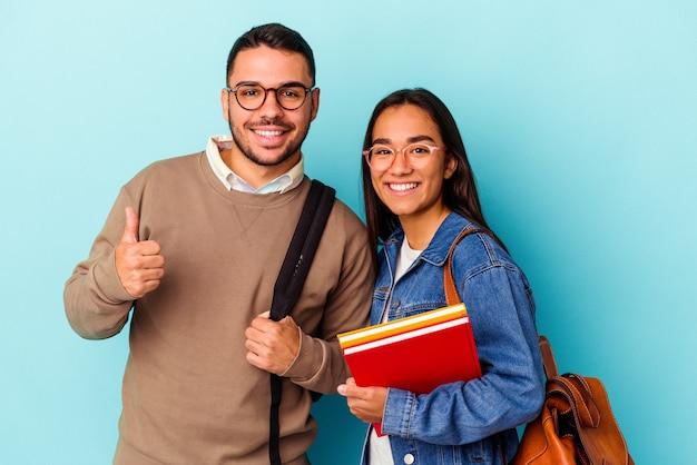 Junges gemischtes rassenstudentenpaar lokalisiert auf blauem hintergrund lächelnd und daumen hochhebend