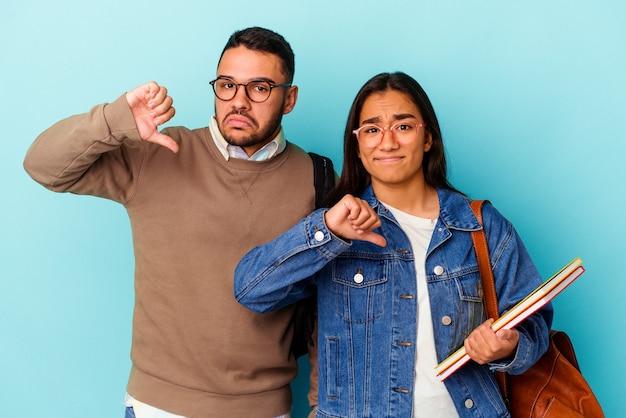 Junges gemischtes studentenpaar isoliert auf blauem hintergrund, das eine abneigungsgeste zeigt, daumen nach unten meinungsverschiedenheit konzept.
