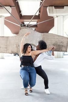 Junges gemischtrassiges paar, das leidenschaftlich zusammen auf einer straße in der innenstadt tanzt