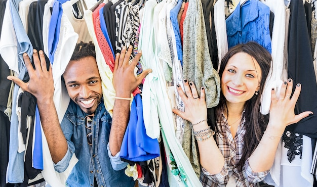 Junges gemischtrassiges paar, das spaß am kleidungsflohmarkt hat - beste freunde, die zeit teilen, die auf billigem verkauf einkaufen - liebhaber, die alltägliche momente genießen - garderobenmodegeschäftkonzept mit glücklichen leuten