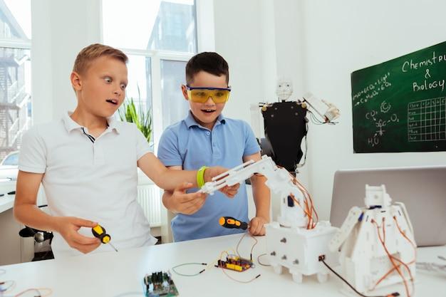 Junges genie. neugierige intelligente schüler, die während eines naturwissenschaftlichen unterrichts an einem projekt arbeiten