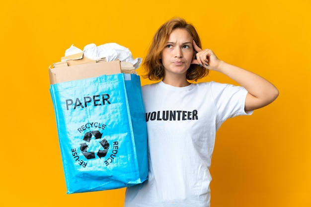 Junges georgisches mädchen, das eine recyclingtüte voller papier hält, um zweifel zu haben und zu denken?